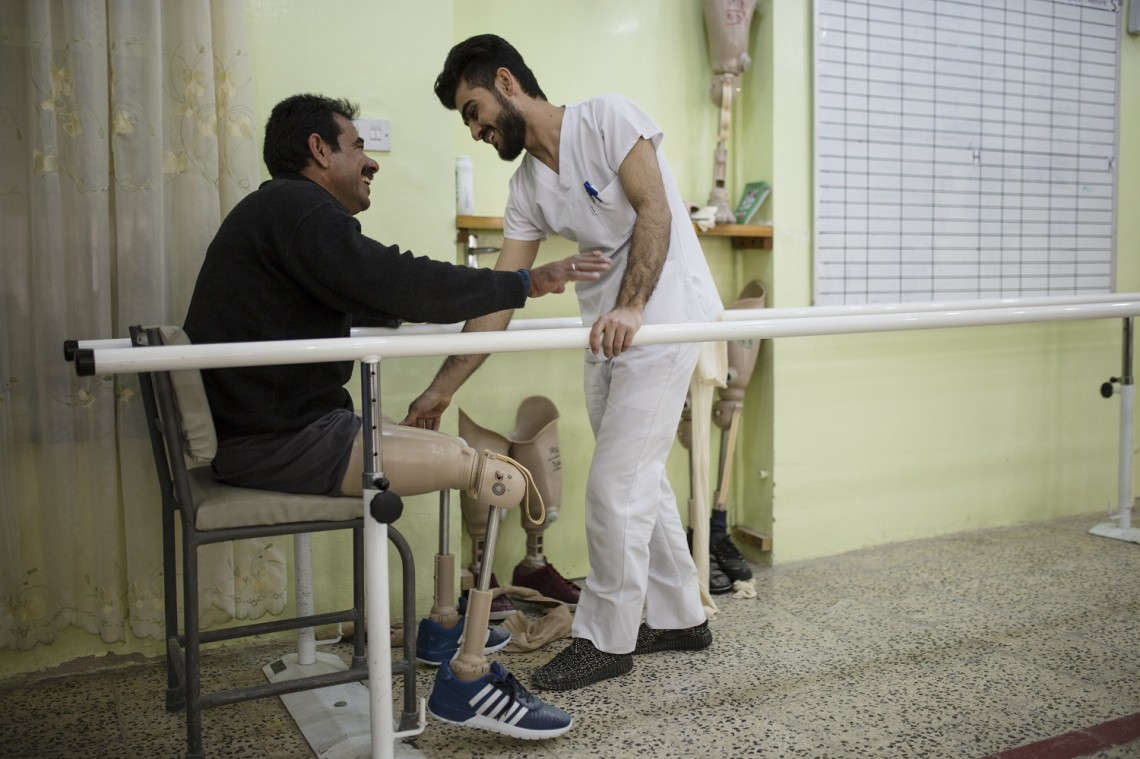 Erbil, Iraq. A man who lost his legs when he drove his car over a landmine in Mosul in 2014 is being assisted by a physiotherapist after he got prosthesis from ICRC orthopaedic center. Photo: Saara Mansikkamäki