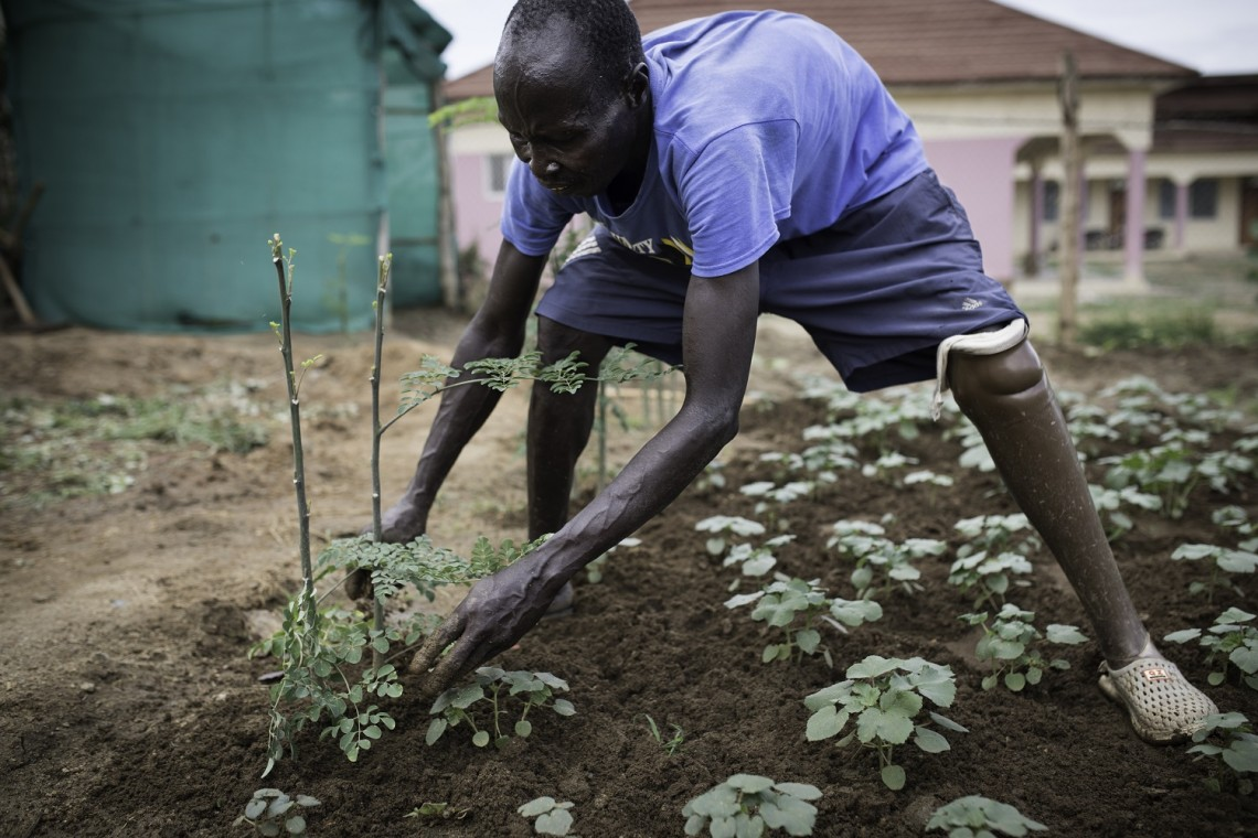 Juba, South Sudan. A former patient of the ICRC physical rehabilitation centre takes care of the garden surrounding the centre. Photo: Florian Seriex