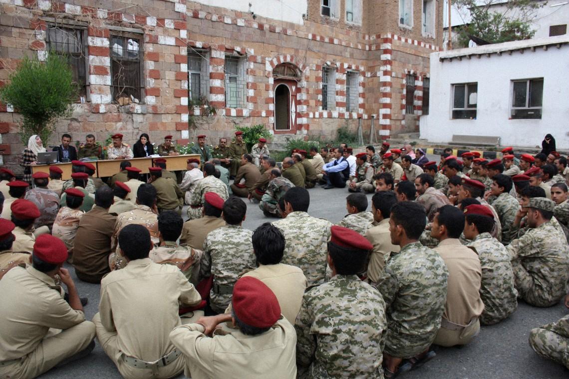 Йемен, Таиз, 2013 г. Сотрудник МККК рассказывает представителям военной полиции о международном гуманитарном праве. (с) V-P-YE-E-01010 / ICRC / Barry, Jessica