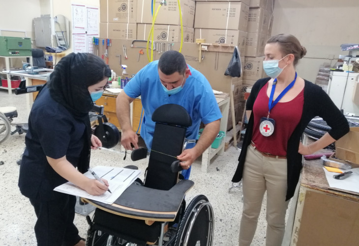Rieke (right) with Shaema (wheelchair technician) and Omar (physio) preparing a specialized wheelchair for a child with cerebral palsy