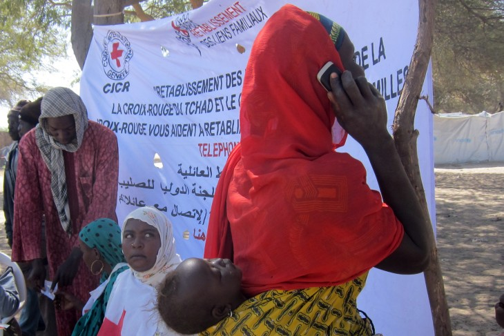 A Nigerian woman who has fled across the border into Chad makes use of an ICRC phone to contact her family.