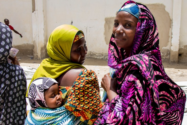 Displaced women and a baby at an ICRC aid distribution in Maiduguri, Nigeria.