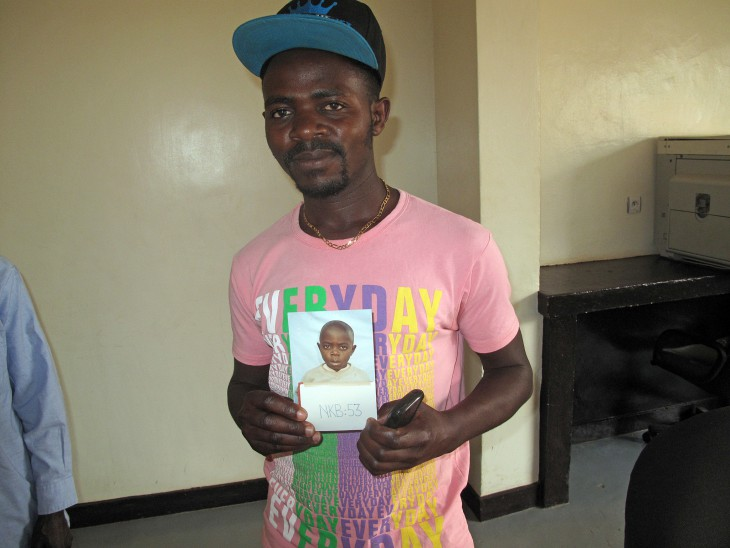 Raymond displays a photo of himself taken in 1994, shortly after the Rwandan genocide separated him from his family.