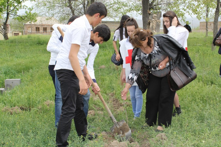Vedi, Armenia. With the support of young Armenian Red Cross volunteers, Mrs Armanush plants a tree in memory of her husband, one of eight people who went missing on the same day in 1992.
