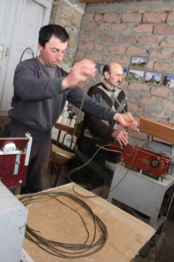 Monaster, South Ossetia. Avtandil (on the left) prepares the wick for his candles.
