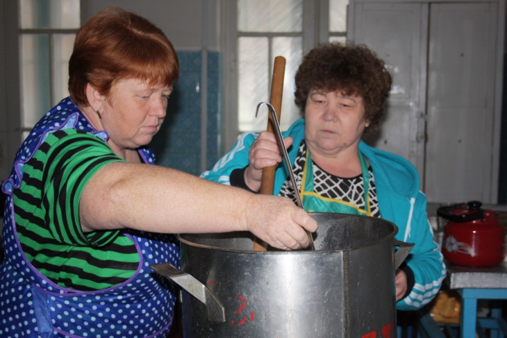 The cooks in the summer camp ladle out tea for their visitors.