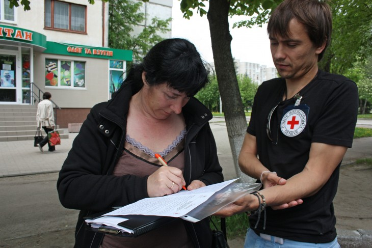 Ruslana writes a reply leaning on Arkadiy's folder.
