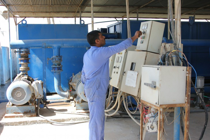 Al-Barakiya, near Abu Aissa, southern Iraq. An operator checks the electrical system for the water treatment plant supplying the village.