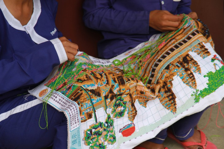 Female detainees embroider an image of Angkor Wat temple.