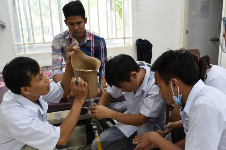 Battambang, Cambodia. A group of student interns learn to fix an artificial limb.
