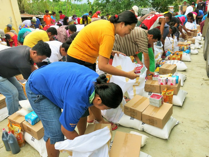 People collect food and essential supplies at a joint ICRC/Philippine Red Cross distribution