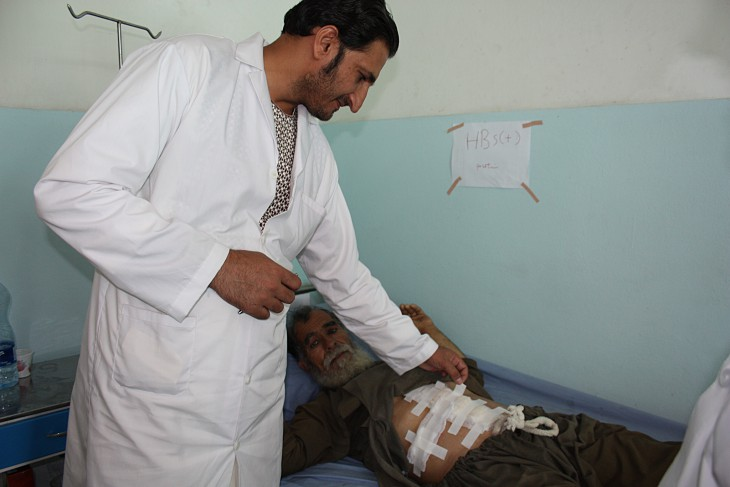 Surgical team head Dr Mirwais Mangal Khail inspects a patient recovering after an operation for a perforated ulcer, carried out using suturing techniques learned from the ICRC team.