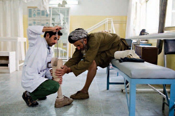 An ICRC orthopaedic technician adjusts a prosthetic leg.