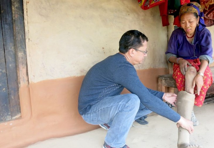 Jagadish Shrestha, health programme responsible at the ICRC Kathmandu inspecting the prosthesis. ©Binod Kafle, ICRC